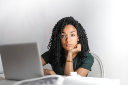 serious ethnic young woman using laptop at home